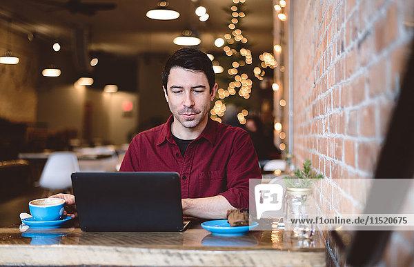 Mann arbeitet am Laptop im Café
