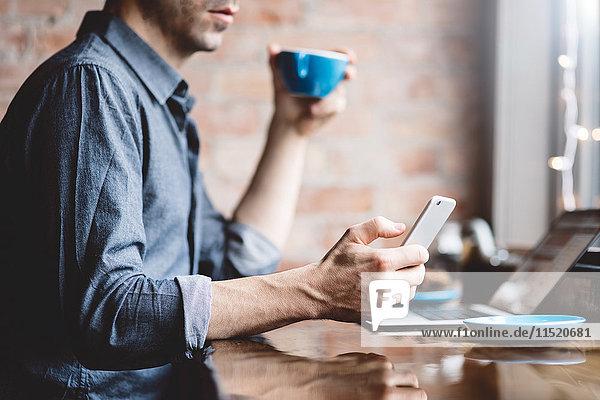 Mann benutzt Mobiltelefon im Café