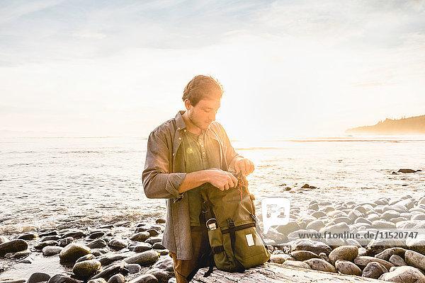 Man searching backpack at beach in Juan de Fuca Provincial Park  Vancouver Island  British Columbia  Canada
