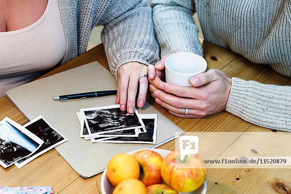 Ausschnittaufnahme eines schwangeren Paares  das sich Schwangerschaftsscans auf dem Tisch ansieht