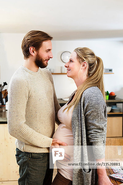 Mann berührt den Bauch der schwangeren Freundin in der Küche