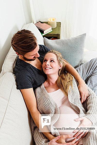 Schwangere Paare im mittleren Erwachsenenalter berühren schwangeren Bauch auf dem Sofa