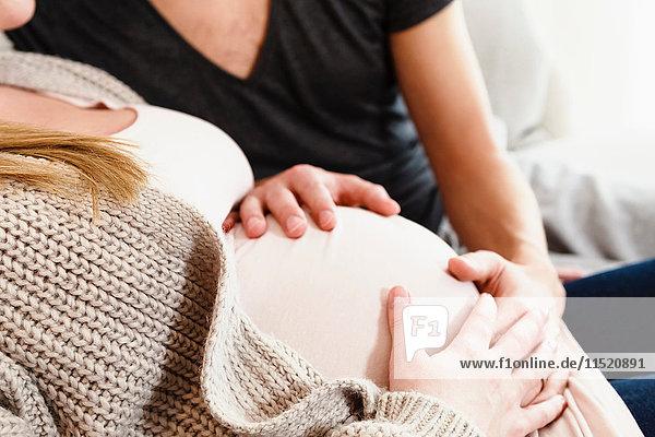 Schnappschuss eines schwangeren Paares im mittleren Erwachsenenalter  das den schwangeren Bauch auf dem Sofa berührt