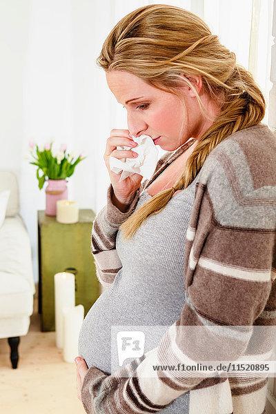 Tränenreiche schwangere Frau berührt Bauch im Wohnzimmer
