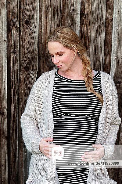 Schwangere Frau im mittleren Erwachsenenalter hält Magen an Holzzaun