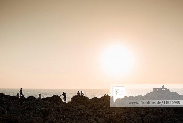 Silhouette of people on rocks at sunset  Ciutadella  Menorca  Spain