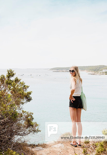 Woman by sea looking over shoulder at camera smiling  Menorca  Spain