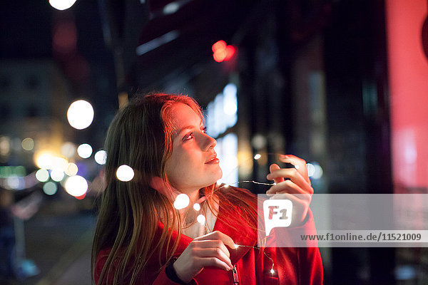 Young woman enjoying bright lights of street  London  UK