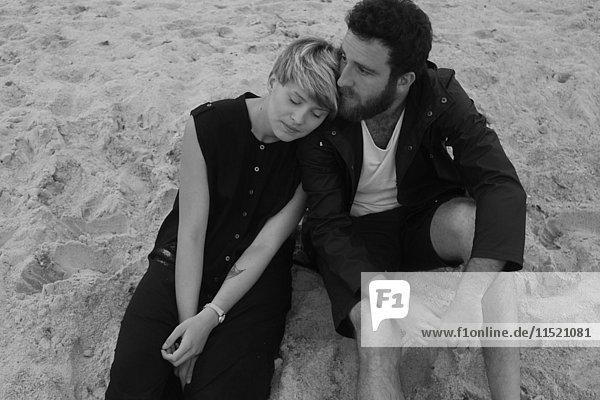 Junges Paar sitzt am Strand und entspannt sich ineinander
