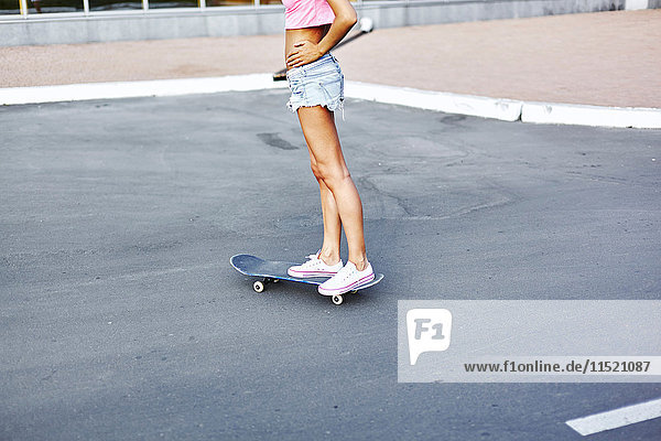 Junge Frau beim Skateboarden entlang der Straße  niedriger Abschnitt