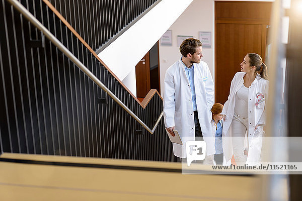 Male and female doctors moving up hospital stairway  talking