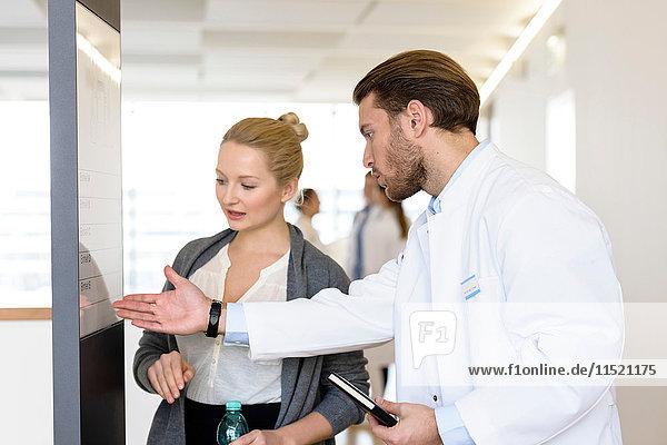 Männlicher Arzt und Frau diskutieren im Krankenhauskorridor