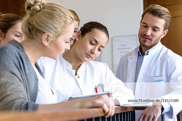 Männliche und weibliche Ärzte sehen sich Krankenakten auf dem Krankenhausbalkon an