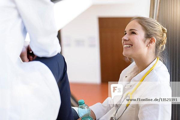 Female doctors taking a break on hospital stairway chatting
