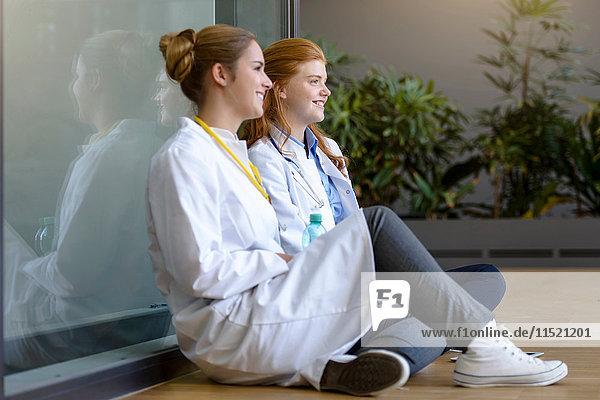 Zwei junge Ärztinnen sitzen auf dem Boden am Eingang des Krankenhauses