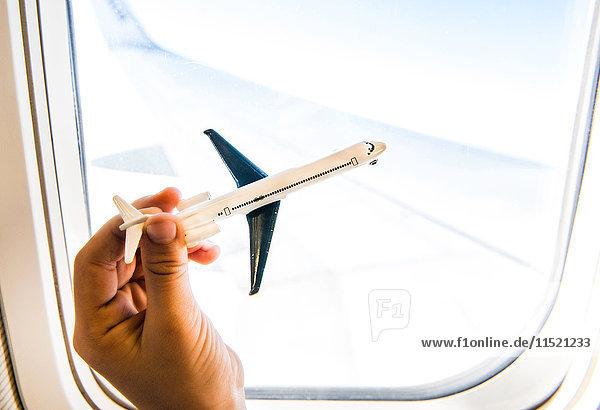 Hand eines Jungen spielt mit Spielzeugflugzeug am Flugzeugfenster