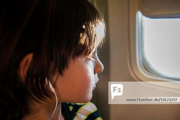 Junge im Flugzeug  der durch ein sonnenbeschienenes Flugzeugfenster schaut Junge im Flugzeug, der durch ein sonnenbeschienenes Flugzeugfenster schaut
