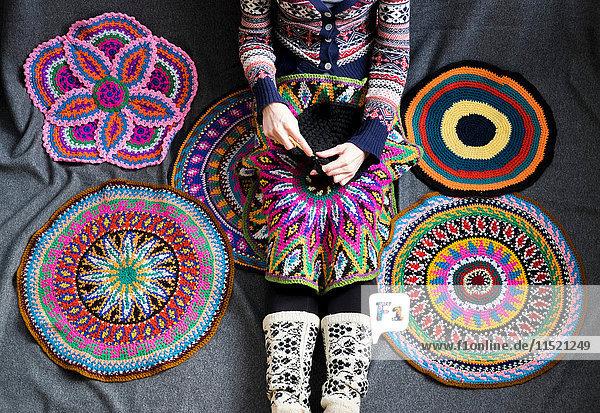 Halsabwärtsansicht einer Frau  die auf dem Boden sitzt und häkelt  umgeben von gehäkelten Kreisen