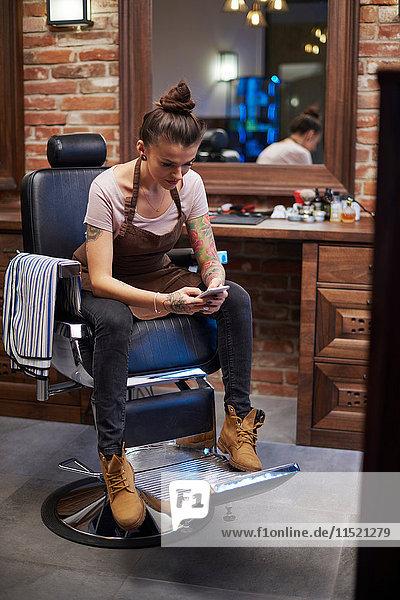 Friseure in Friseursalon schreiben SMS auf Smartphone