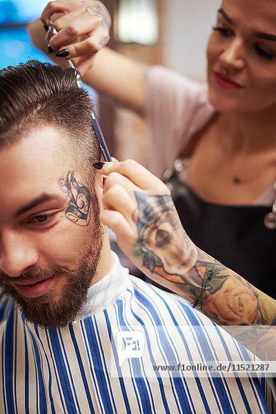 Friseur schneidet den Kunden die Haare