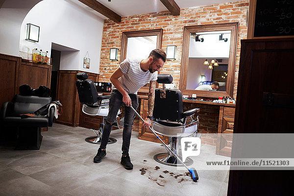 Friseur in Friseursalon fegt Haare