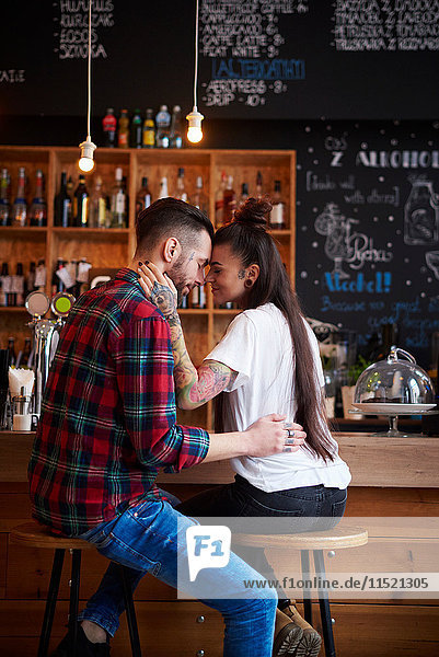 Couple on stools in coffee shop face to face smiling