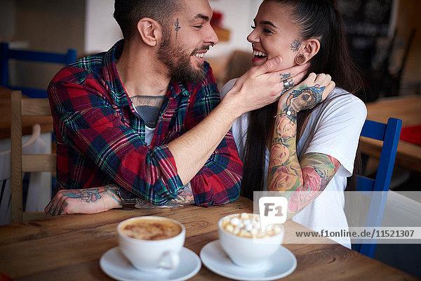 Paar im Café von Angesicht zu Angesicht lächelnd