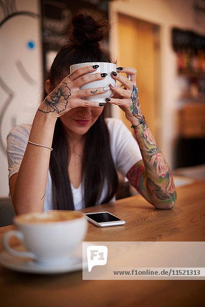 Tätowierte Frau hält Tasse und schaut auf Smartphone