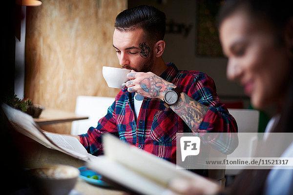 Paar trinkt Kaffee und liest Zeitungen