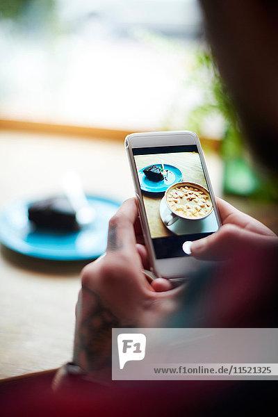 Mann fotografiert Kuchen auf heißer Schokolade mit einem Smartphone