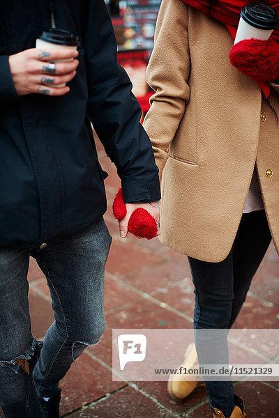 Paar mit Einwegbechern  die Hände halten
