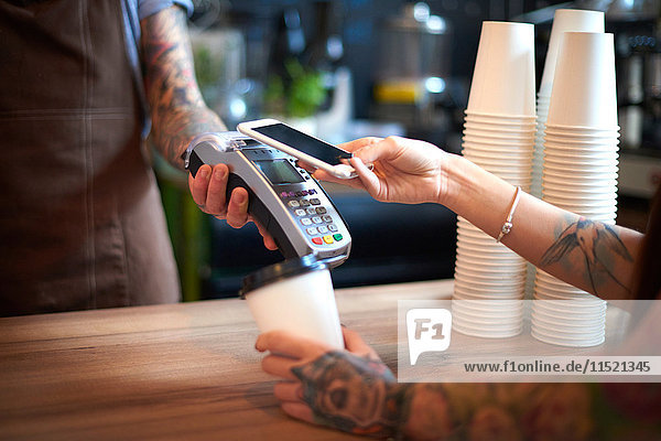 Customer paying for her coffee by mobile payment