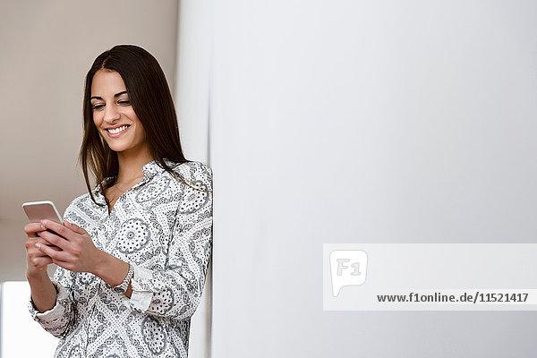 Junge Geschäftsfrau lehnt an Bürowand und schaut auf Smartphone