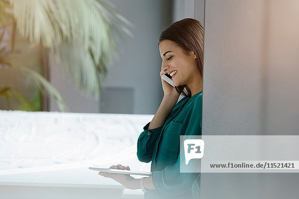 Young businesswoman looking at digital tablet and talking on smartphone in office