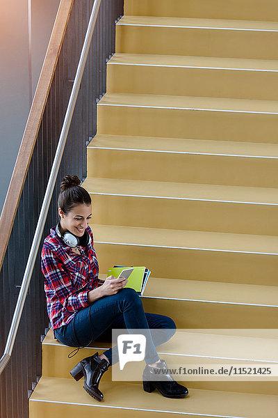 Junge Studentin sitzt auf der Treppe und schaut auf ein Smartphone