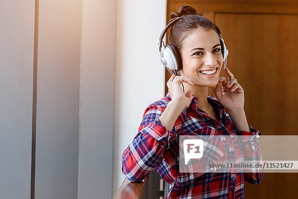 Portrait of young woman in plaid shirt in corridor listening to headphones