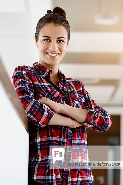 Portrait of young woman in plaid shirt in corridor with arms folded