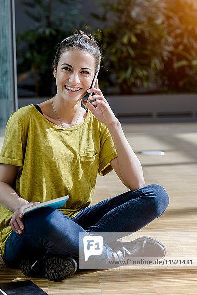Porträt einer jungen Studentin  die im Schneidersitz im Freien sitzt und sich mit einem Smartphone unterhält