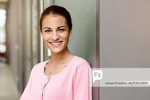 Junge Geschäftsfrau in rosa Bluse im Bürokorridor