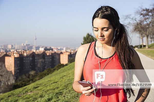 Sportlerin mit Kopfhörer über ihr Telefon