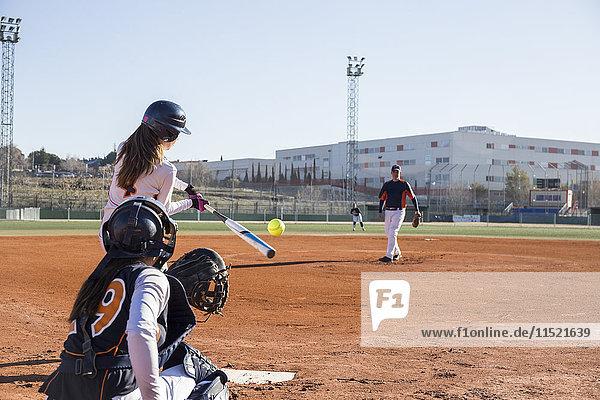 Weiblicher Teig  der den Ball während eines Baseballspiels trifft.
