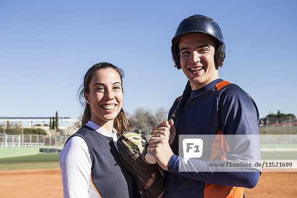 Portrait of smiling male and female baseball player
