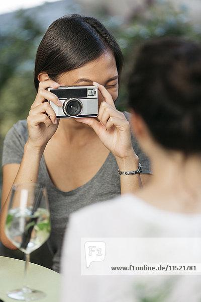 Junge Frau beim Fotografieren ihrer Freundin mit Kamera im Straßencafé