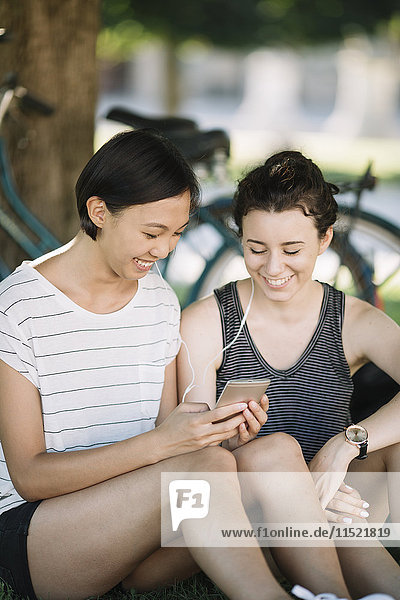 Two friends sitting in city park listening music together with earphones