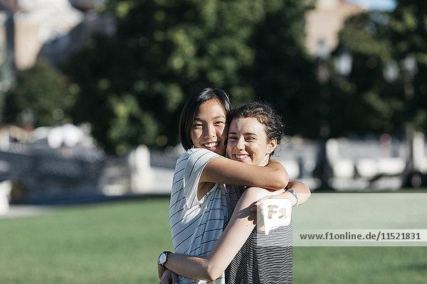 Porträt von zwei besten Freunden  die sich im Park umarmen