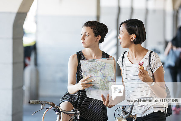 Italy  two young tourists with bicycles and map