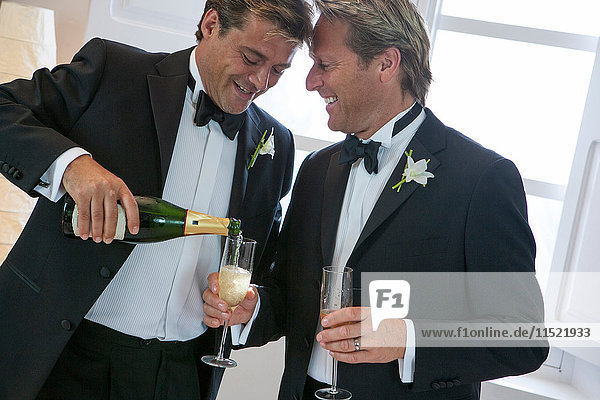Newlywed mature male couple pouring champagne