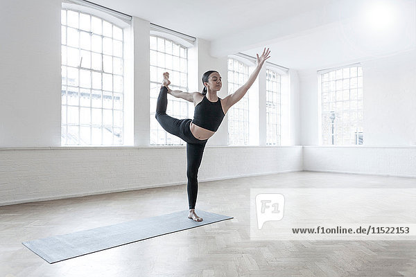 Woman in dance studio leg raised  stretching
