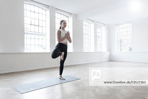 Frau im Tanzstudio auf einem Bein stehend in Yogastellung