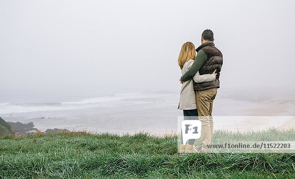 Paarumarmungen an der Küste an einem nebligen Wintertag mit Blick auf die Aussicht
